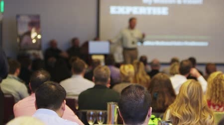 "motivasyonel : a shot from the back of the room of a speaker talking with the words ""expertise"" on the powerpoint. no faces are shown."