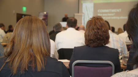"beszélő : a shot from the back of the room of a speaker talking with the words ""expertise, efficient and passion"" on the powerpoint. no faces are shown, back of peoples heads. Stock mozgókép"