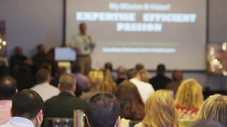 "motivasyonel : a shot from the back of the room of a speaker talking with the words ""expertise, efficient and passion"" on the powerpoint. no faces are shown."