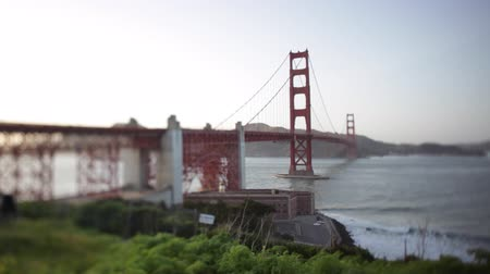 a slider shot moving through a hole in the fence of the golden gate bridge