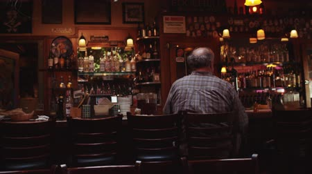 tek başına : a man sits alone at a bar by himself Stok Video