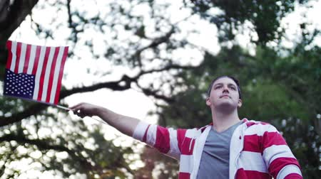 четверть : a slow motion shot of a man waving an american flag angled upward from below