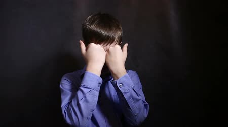 pŁacz : Teenage boy crying upset closed eyes with his hands in a blue shirt, studio  background Wideo
