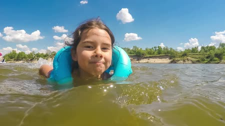 rzeka : the girl child is learning to swim in the river lifejacket summer blue sky happiness childhood  Video Wideo
