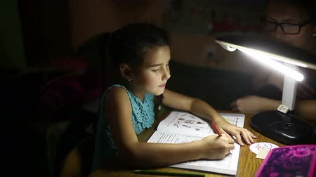 tablo : teen girl in the evening doing  homework lessons draws light from the lamp