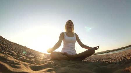 meditação : woman in white  sitting on sand meditation healthy lifestyle sunset sun goes down, silhouetted against the sky Yoga Vídeos