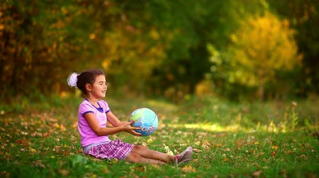 global : girl  teen sitting  green grass playing studying Globe happy