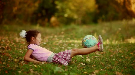 global : teen  girl brunette  sitting on green grass playing studying Globe happy