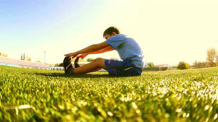 stopy : Teenage  doing boy workout footballer athlete sits on a grass sports gymnastics
