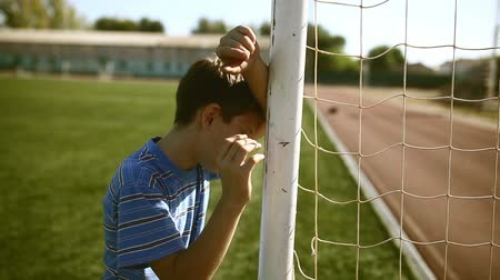 göller : Teen upset  defeat boy by knocking goal goal post net stadium turf