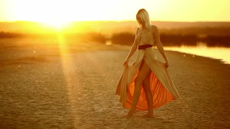 brown dress : young  seductive girl woman dress develops go at smiling at sunset sexy yellow desert sand yellow background Stock Footage