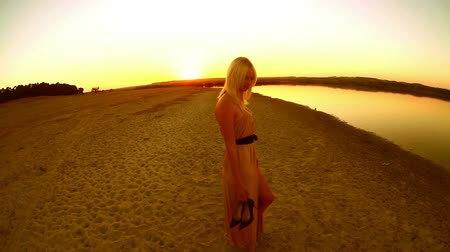 brown dress : young  sexy seductive girl woman dress develops go at smiling at sunset yellow desert sand yellow background Stock Footage