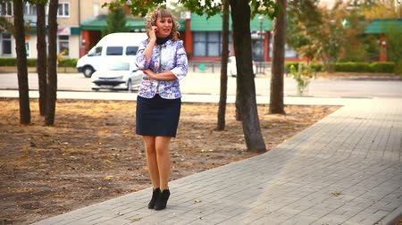 otuzlu yıllar : full fat  middle-aged woman on phone in the park behind the cars drive lifestyle Stok Video