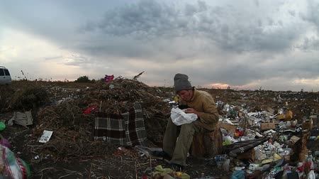 csavargó : man unemployed homeless dirty looking food waste in dump landfill  social  video Stock mozgókép