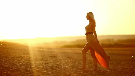 giydirmek : young  seductive girl sexy woman dress develops go at smiling at sunset yellow desert sand yellow background