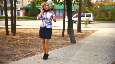 otuzlu yıllar : full fat  middle-aged on phone woman in the park behind the cars drive lifestyle