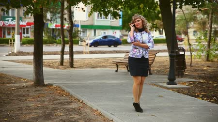 otuzlu yıllar : full fat  middle-aged on phone in the park woman behind the cars drive lifestyle
