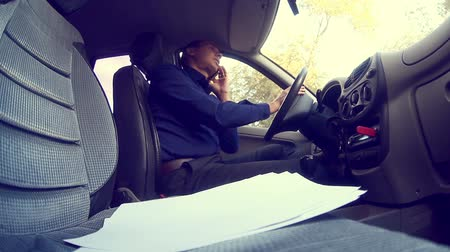 pojistka : man businessman talking on the phone in car keeps documents insurance business negotiations Dostupné videozáznamy