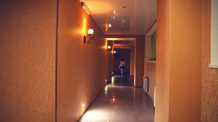 прихожая : employee  of hotel manager is woman in the evening along the corridor yellow light