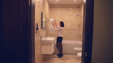 banyo : Maid  makes woman cleaning bathroom towel straightens