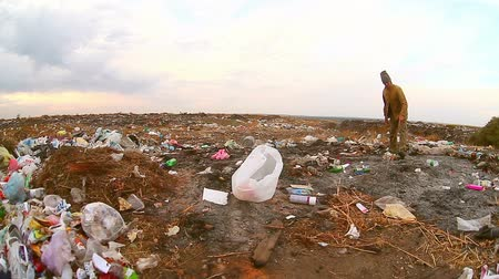 guba : homeless  man looking for food in the garbage dump food waste environmental protection Stock mozgókép