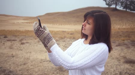 mittens : woman girl smartphone makes self phone mittens pullover sitting on dry tree nature autumn Stock Footage