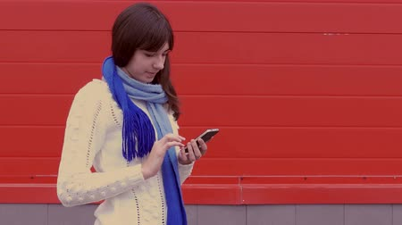 başörtüsü : woman girl holding a smartphone phone in a jacket and scarf social networks media