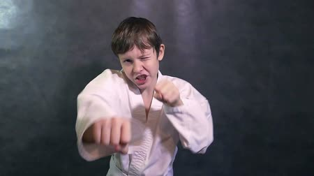 sztuki walki : boy teenage karate in kimono fight hands waving fists slow motion
