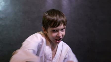 sztuki walki : karate boy fighting kid punches at the camera slow motion