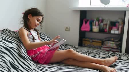 pré adolescente : teen girl playing tablet game internet sitting on bed