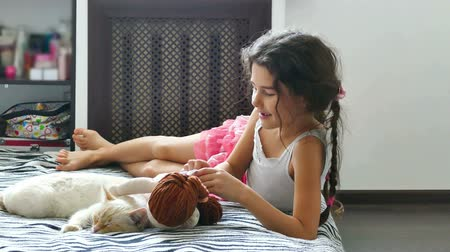nevinný : teen girl play with a doll cat sleeps next
