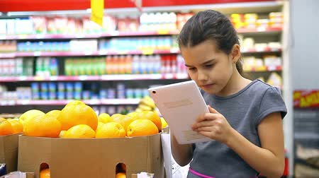 купить : girl teen with tablet in supermarket to buy orange