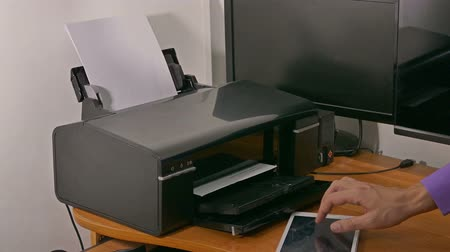 másológép : man businessman in office prints documents on printer typing on the tablet