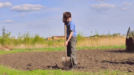 Łopata : farmer  weary boy digs ground old dirty shovel on dry ground video slow motion