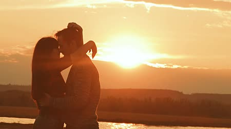 kapcsolatok : man and woman laughing and hugging at sunset slow motion video Stock mozgókép
