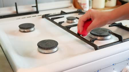 fogão : woman washes a gas stove in cleaning the kitchen