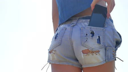 atleta : The girl takes out a smartphone from her pocket of shorts. back view