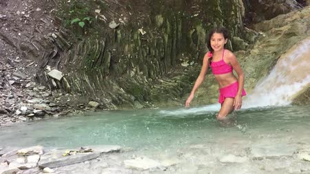 girl teenager bathing in swimsuit in the lake in the mountains waterfall. mountain river girl teenager