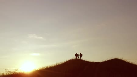 people group of tourists walking on travel top of a sunset silhouette mountain. slow video tourists people group go nature