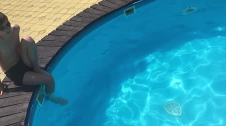 boy in the pool playing slow motion video Vídeos