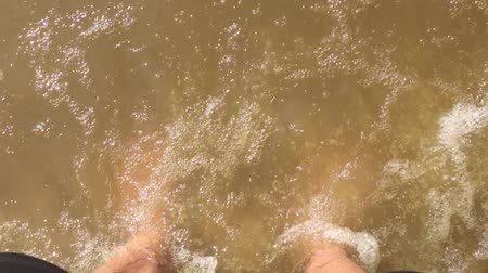 feet waves of sea slow motion video. male tourist is standing with his feet in the ocean of water splashing on his feet