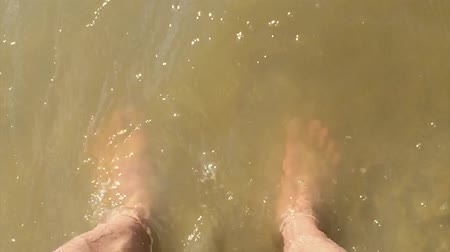 feet waves of sea slow motion video. male tourist man is standing with his feet in the ocean of water splashing on his feet