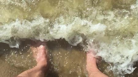 feet waves of sea slow motion video man. male tourist is standing with his feet in the ocean of water splashing on his feet