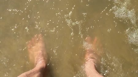 feet waves of sea slow motion video. male tourist is standing man with his feet in the ocean of water splashing on his feet