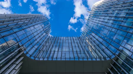 glass structure : Time lapse, looking up at a glass-covered skyscraper, reflecting the blue sky and passing clouds