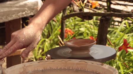 esculpir : Potter works on a potters wheel, produces coffee cups Vídeos