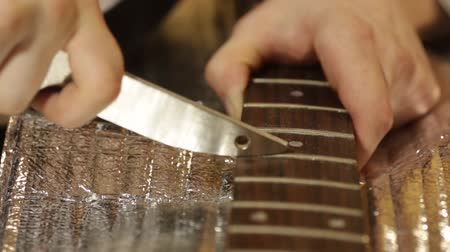 készítő : Guitar maker grinds musical frets on the fingerboard of the guitar