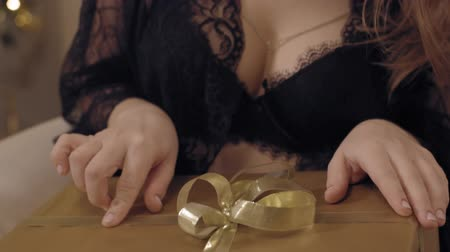 Close up shot of hands of young beautiful woman in black lace peignoir playing with ribbon on new year gift sitting in chair against christmas tree.