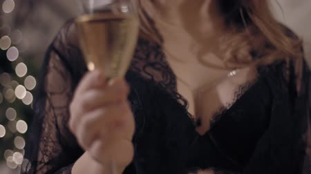Close up shot of wineglass with sensual breasts in black lingerie on background.
