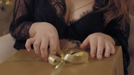 Close up shot of hands of young sensual woman in black lace peignoir playing with her new year gift sitting in chair against christmas tree.